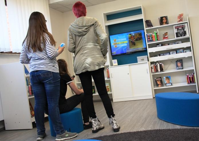 Zwei Mädchen spielen bei der Eröffnung der neuen Jugendecke in der Stadtbücherei Nintendo