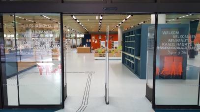 Ein offener Eingang und eine Begrüßung in mehreren Sprachen empfangen die Bibliotheksnutzer. Zudem führt ein takiles Bodenleitsystem in die Bibliothek und direkt zur Theke.