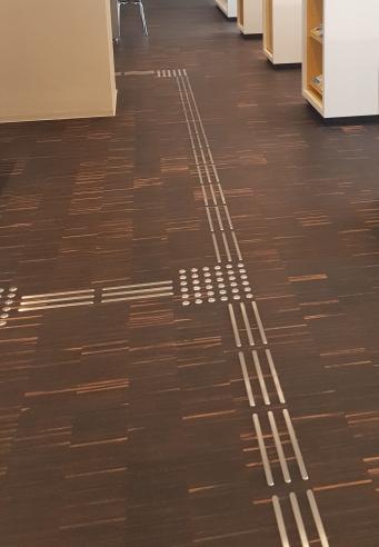 Die taktilen Streifen auf dem Boden führen durch die Bibliothek. Quadratische Aufmerksamkeitsfelder machen Abbiegungen und Gefahrenstellen kenntlich. (Stb. Ingelheim)
